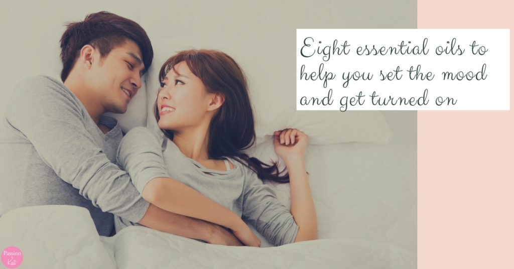 Asian couple cuddling in bed looking at each other lovingly and holding hands. | Aphrodisiac Essential Oils to Boost your Libido _ Passion by Kait