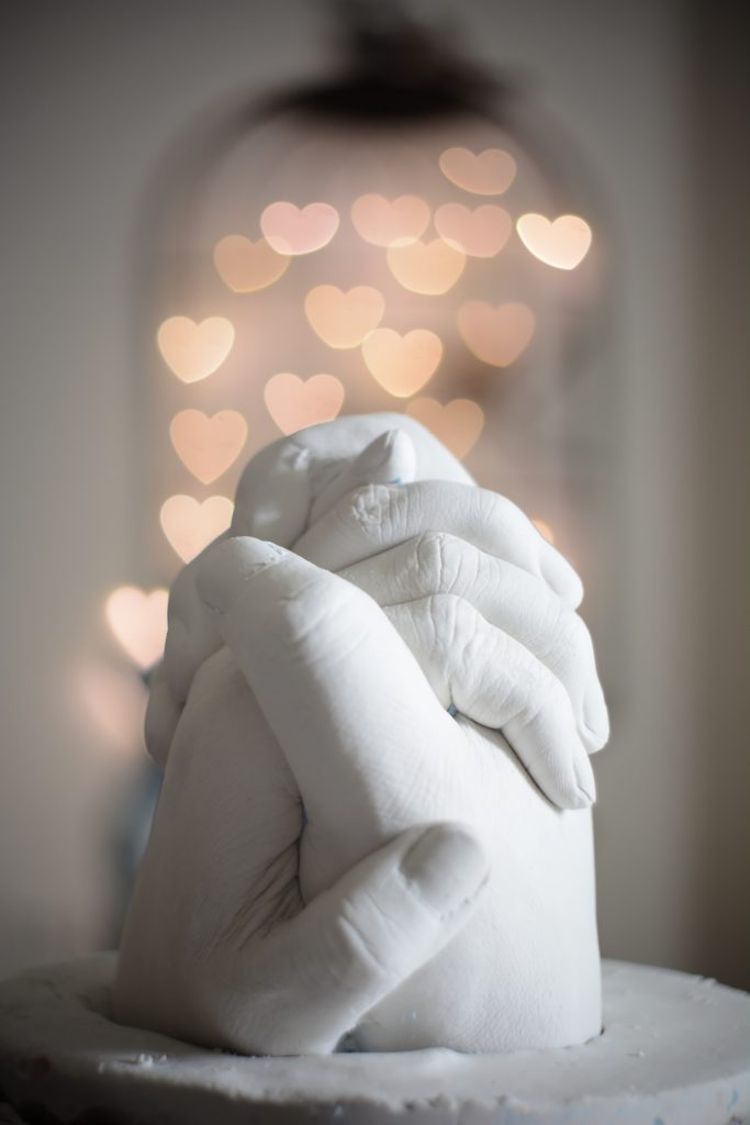 Alabaster sclupture of clasped hands with hanging heart-shaped lights in the background. Love Advice for a Good Relationship | Passion by Kait